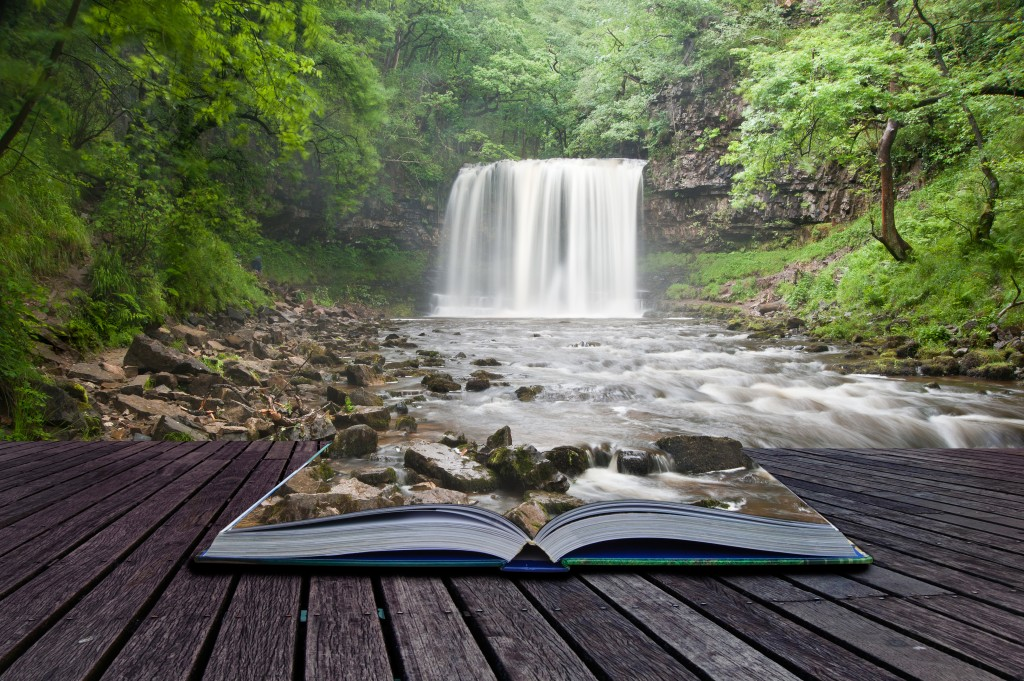 Creative composite image of waterfall in woods in pages of magic book